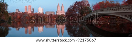 Beautiful Fall dawn panorama in Central Park. Reflections of Bow bridge and New York Skyscrapers in the Lake. - stock photo