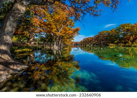 Beautiful Fall Foliage Surrounding the Clear Frio River, Texas. - stock photo