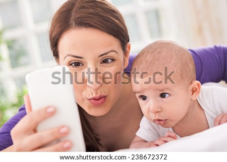 Beautiful family at home taking photo of themself - stock photo