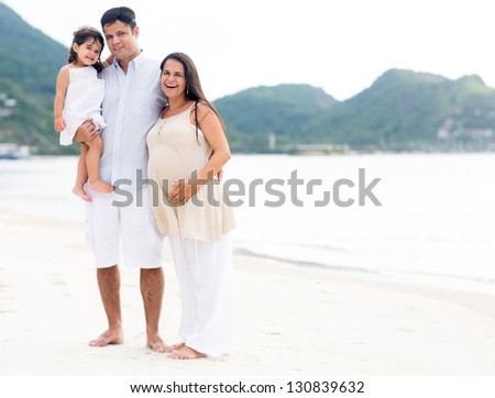 Beautiful family at the beach with pregnant woman - stock photo