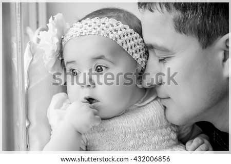 Beautiful family closeup. Father kissing newborn daughter girl. Happy baby childhood. Background, closeup, macro. Black and white photo - stock photo