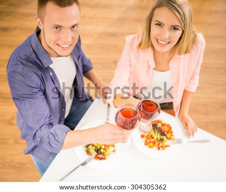 Beautiful family couple having dinner together. They are drinking wine and looking at camera. Top view. - stock photo