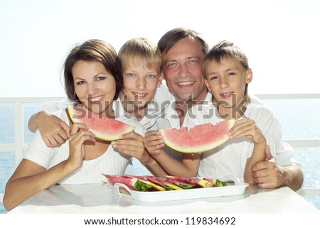 beautiful family eating watermelon in the background of the sea - stock photo