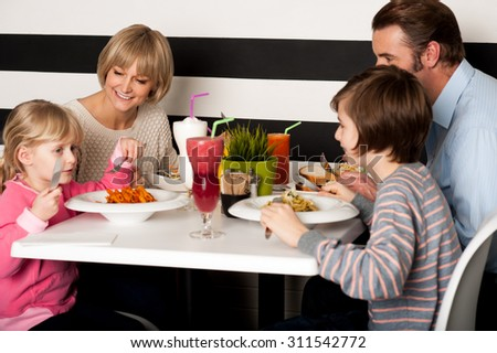 Beautiful family having great time at restaurant - stock photo