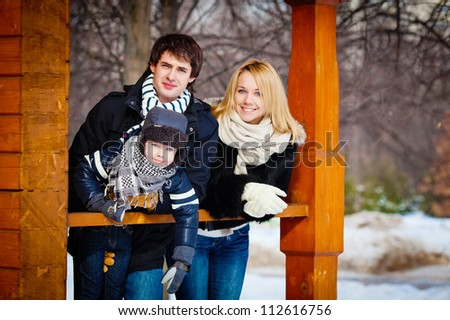 Beautiful family in warm clothes standing on the porch of his house in winter, horizontal photo