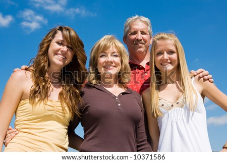 Beautiful family of grandparents and granddaughters against a blue sky. - stock photo