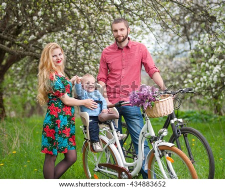 Beautiful family on a bicycles in the spring garden. Mother holding her bike and baby sitting in bicycle chair, in the basket lay a bouquet of lilacs, against the background of blooming trees