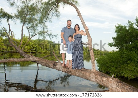 Beautiful family outdoors by the lake smiling on a tree  - stock photo