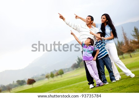 Beautiful family outdoors in a green field pointing