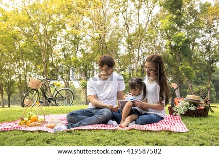 Beautiful family portrait  ,Happy Asian Family In Garden - stock photo