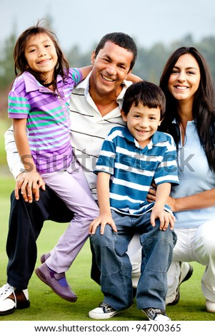 Beautiful family portrait outdoors looking happy and smiling - stock photo