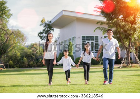 Beautiful family portrait smiling outside their new house with sun light - stock photo