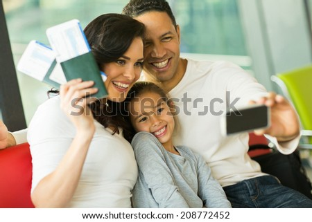 beautiful family taking selfie with smart phone while waiting for their flight at airport - stock photo