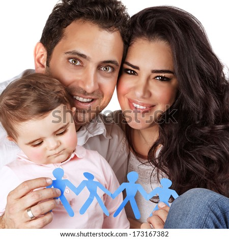 Beautiful family together isolated on gray background, happy young parents carry little daughter, people-shaped blue paper bonding toy in hands, togetherness concept   - stock photo