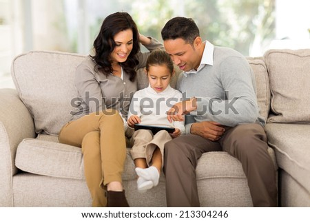 beautiful family using tablet computer at home - stock photo