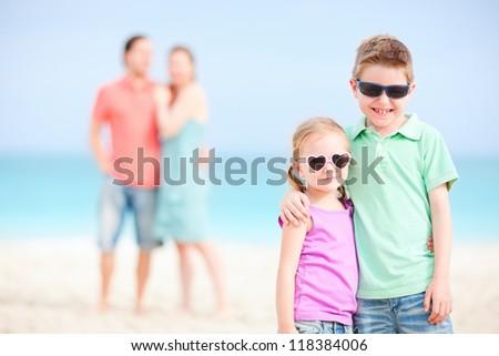 Beautiful family with two kids enjoying beach vacation - stock photo