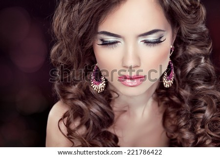 Beautiful fashion brunette woman model with wavy long hair and fashion earrings. Professional makeup. - stock photo