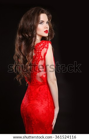 Beautiful fashion elegant woman in red dress isolated on black background. Makeup. Long wavy hair style. - stock photo