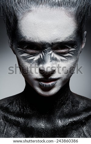 Beautiful  fashion face with black and white artistic ethnic makeup on her face - stock photo
