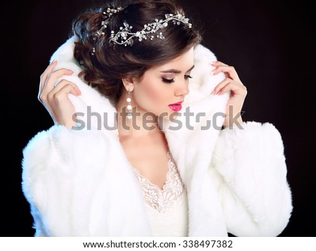Beautiful Fashion Girl in White Mink Fur Coat. Jewellery. Winter portrait. Beauty woman model with elegant hairstyle and makeup posing isolated on dark studio background. - stock photo