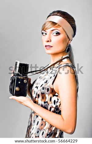 Beautiful fashion girl on the white background with camera - stock photo