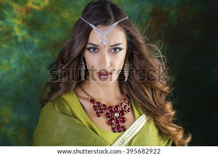 Beautiful fashion Indian woman portrait with oriental accessories earrings. Arabic girl with beauty jewels. Hindu model with perfect make-up. India