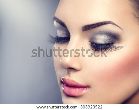 Beautiful Fashion Luxury Makeup, long eyelashes, perfect skin facial make-up. Beauty Brunette model woman holiday make up close up. Eyelash extensions, false eyelashes.  - stock photo