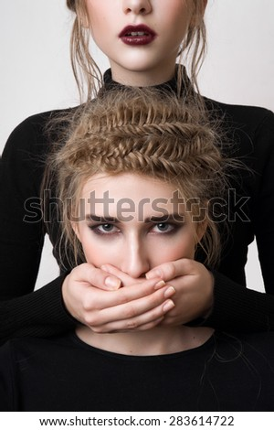 Beautiful fashion model covering blonde's mouth - stock photo