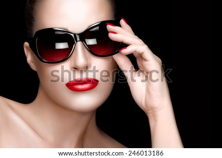 Beautiful fashion model girl with hand on her stylish oversize sunglasses looking at camera. Professional makeup and manicure. High fashion portrait over black background. Beauty and fashion concept.