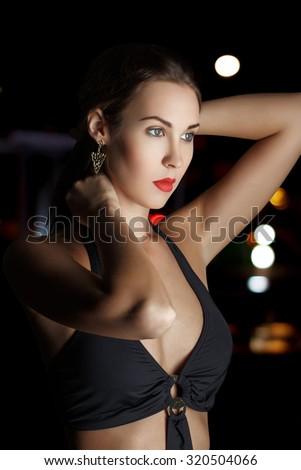 Beautiful fashion model holding hair at night - stock photo