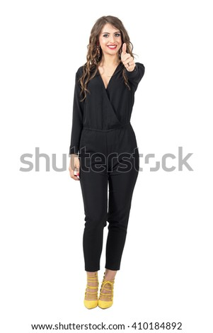 Beautiful fashion model in black jumpsuit with thumb up gesture. Full body length portrait isolated over white studio background. - stock photo