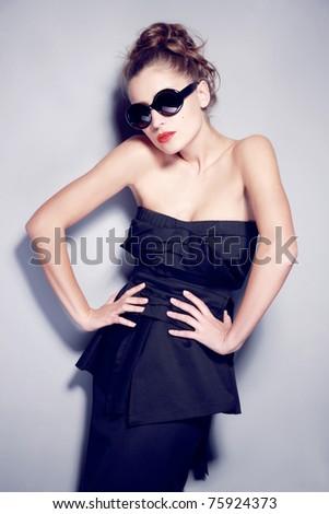 Beautiful  fashion model in studio on grey background - stock photo