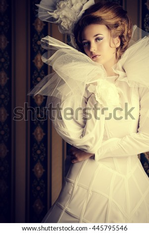Beautiful fashion model in the refined white dress and elegant hat. Vintage style. Art project. - stock photo