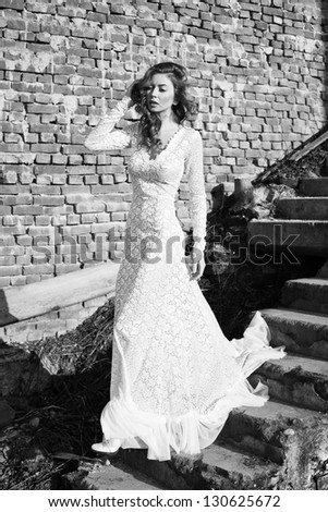 Beautiful fashion model in white dress posing outdoor - stock photo