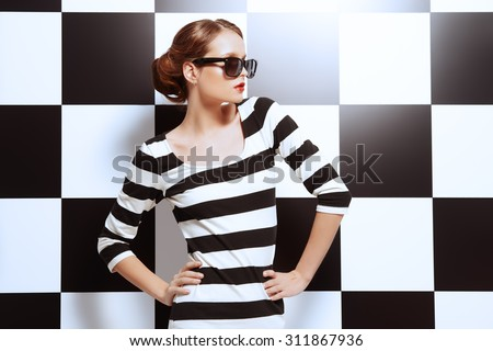 Beautiful fashion model posing in dress in black and white stripes on a background of black and white squares. Beauty, fashion concept. Business style. - stock photo