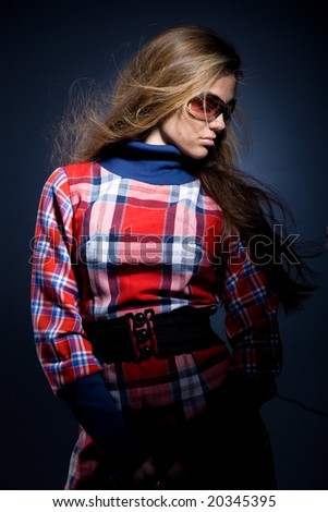 Beautiful fashion model with long hair in checkered dress and glasses - stock photo