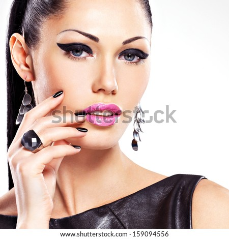 Beautiful fashion sexy woman with black nails at pretty face. Pretty girl model with stylish bijouterie of  silver color.
