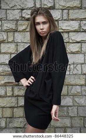beautiful fashion woman against a stone wall - stock photo
