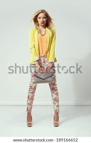 Beautiful fashion woman holding a handbag. Colorful clothes - stock photo