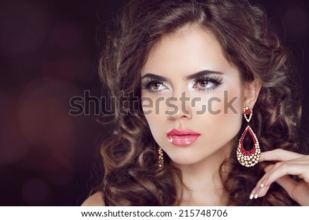 Beautiful fashion woman model with wavy long hair and fashion earrings