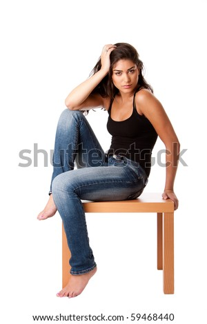 Beautiful fashion woman sitting on wooden table wearing blue denim jeans and black tank top, isolated. - stock photo
