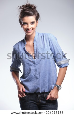 Beautiful fashion woman smiling for the camera with her hands in pocket.