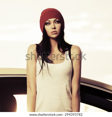 Beautiful fashion woman standing by her car - stock photo