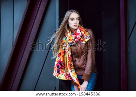 Beautiful fashion woman wearing leather coat and scarf posing against modern wall - stock photo