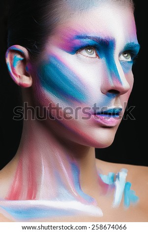 Beautiful fashion woman with bright color face art and body art. Paint on face. Creative portrait - stock photo