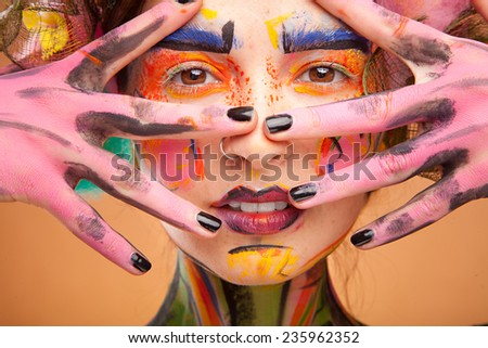 Beautiful fashion woman with bright color face art and body art. Paint on face. Posing in studio. Creative portrait on yellow background. - stock photo