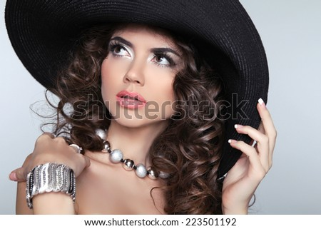 Beautiful Fashion Woman with Curly Long Hair. Elegant lady in hat. Studio photo - stock photo