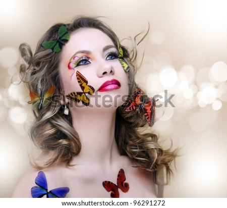 beautiful fashion woman with professional make-up surrounded by butterfly - stock photo