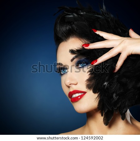 Beautiful fashion woman with red nails, creative hairstyle and makeup - Model posing in studio - stock photo