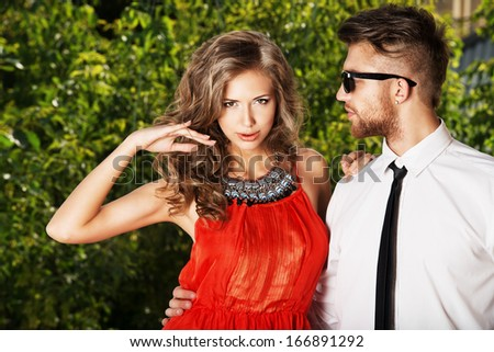 Beautiful fashionable couple standing outdoor. - stock photo